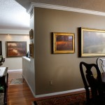 "A trio of Brent Cotton landscapes in the dining room of Bullard's Denver condominium, with the ""million-dollar wall"" in the background"