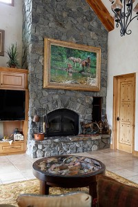 A large painting by Ed Kucera hangs above the living room fireplace.