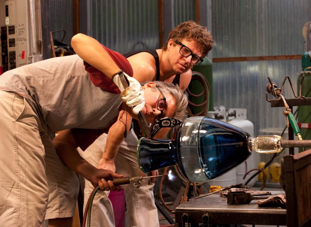 Preston Singletary (front) and Dante Marioni at work in the studio.